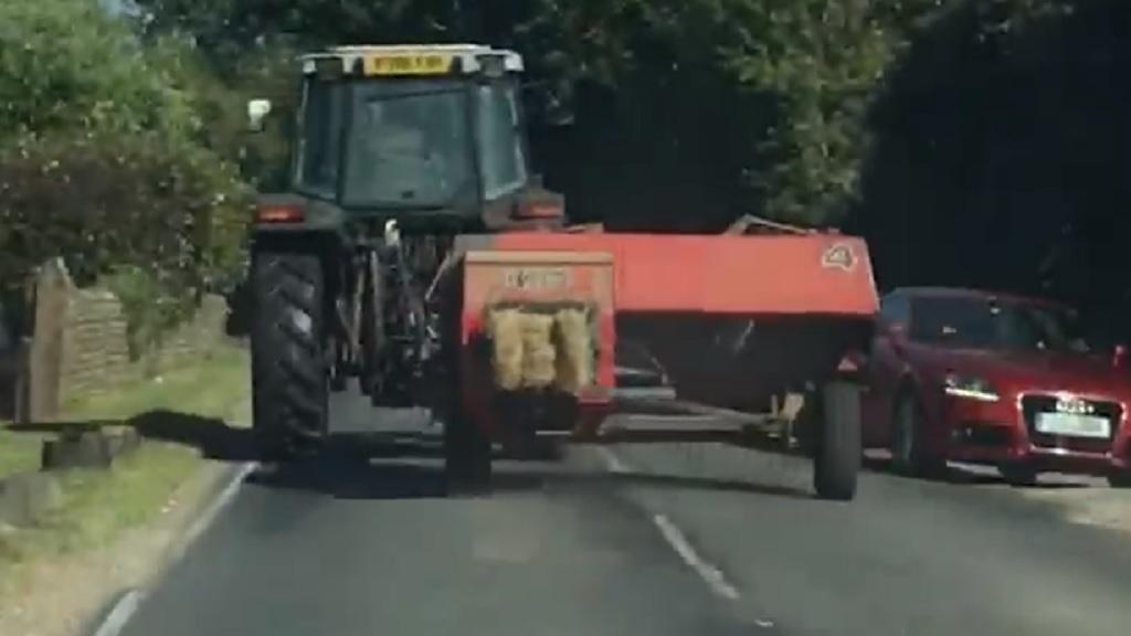Safety reminder after video captures cars swerving to avoid tractor and baler