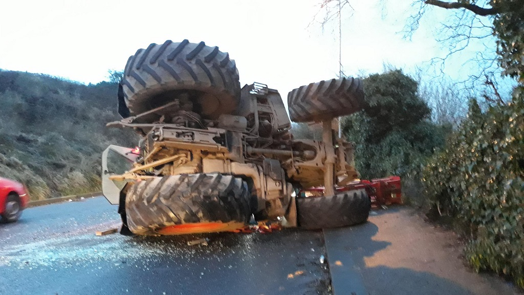 Man taken to hospital after tractor overturns on busy road