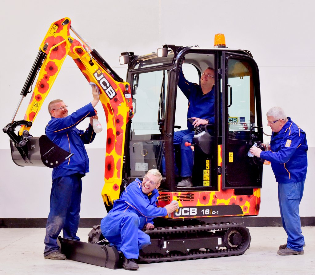JCB employees putting finishing touches to the machine's unique poppy design livery.