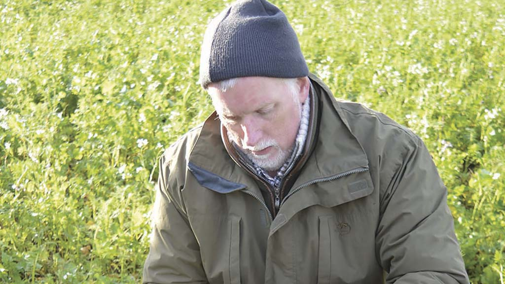 Neil Fuller examines soil at Graham Potter's farm.