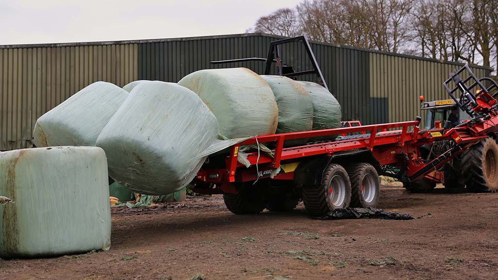 Unloading takes two minutes. The rear of the trailer lowers and the headboard pushes the bales off.