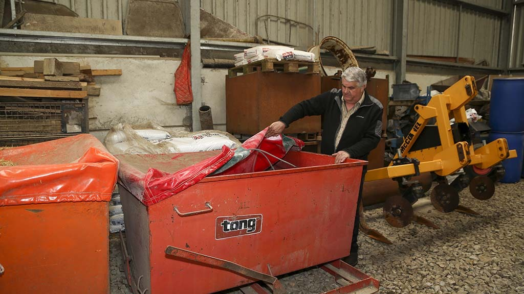 Cattle feed is stored in a skip and covered with a rubber sheet to keep badgers out